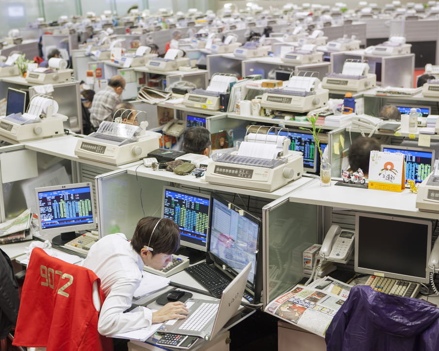Picture of a crowed stock exchange with people sitting in small cubicles