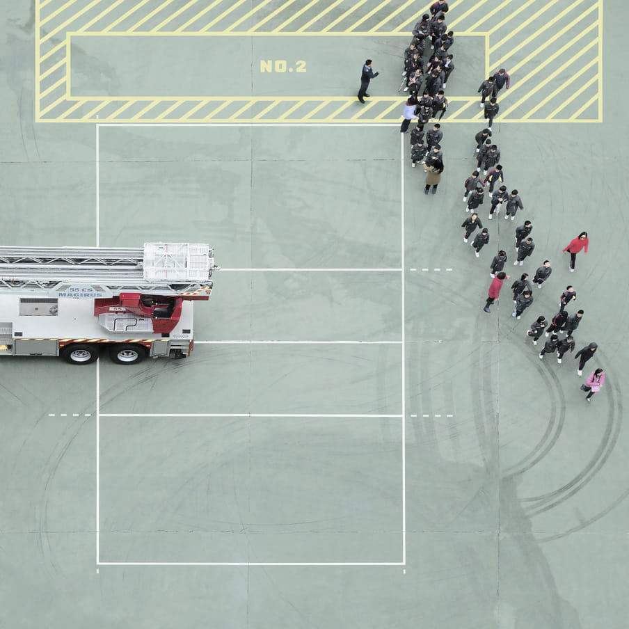 Photograph taken from above on a mint green court showing a group of people near a firetruck.
