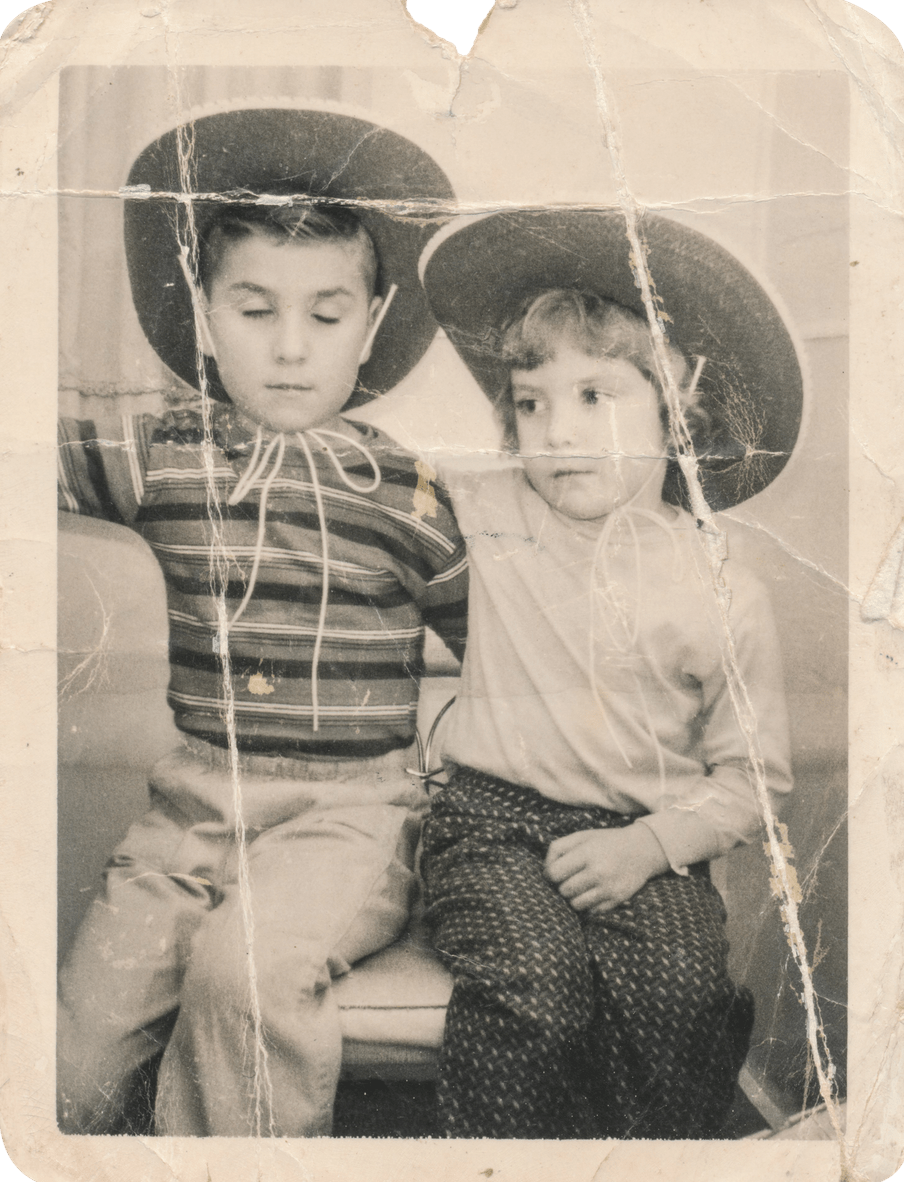 Old damaged sepia coloured photograph of two young children with an arm over the other, seated, and wearing big cowboy hats