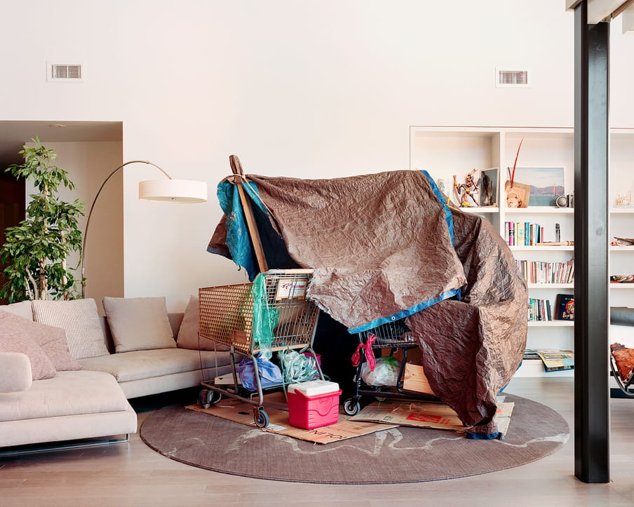 Photo of a living room of a middle or upper class house, with a homeless shelter built from shopping carts and tarp