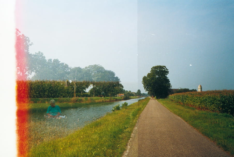 Photo of a road with a river next to it. Due to double exposure, a man seemingly sits in the middle of the river. A light flare cuts of the image on the left side.