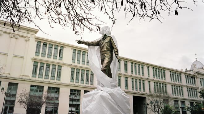 A half-covered statue being restored in Athens in front of a government building.