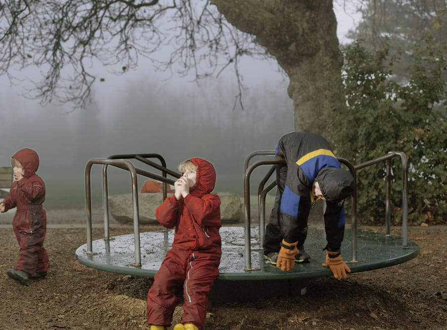Photo of boys playing, wearing winter suits, on a playground