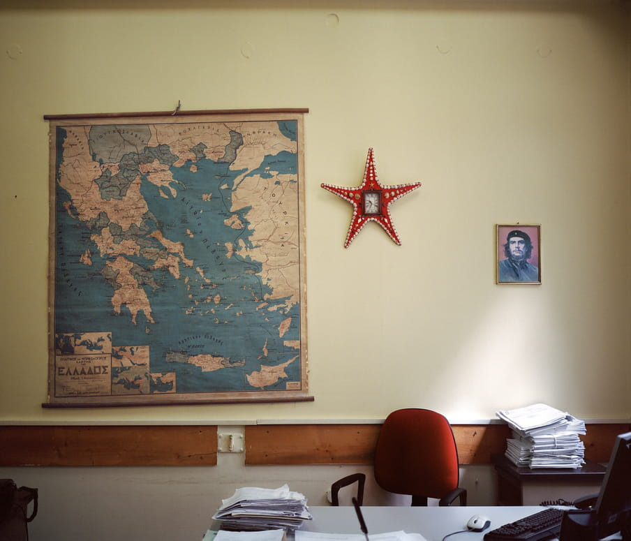 A map of Greece on the wall of an empty office beside a portrait of Che Guevara.