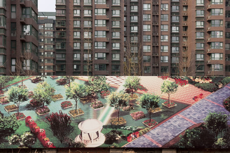 Huge pannel showing a photograph of a surreal aqua garden with pink and purple colours in front of brown buildings.