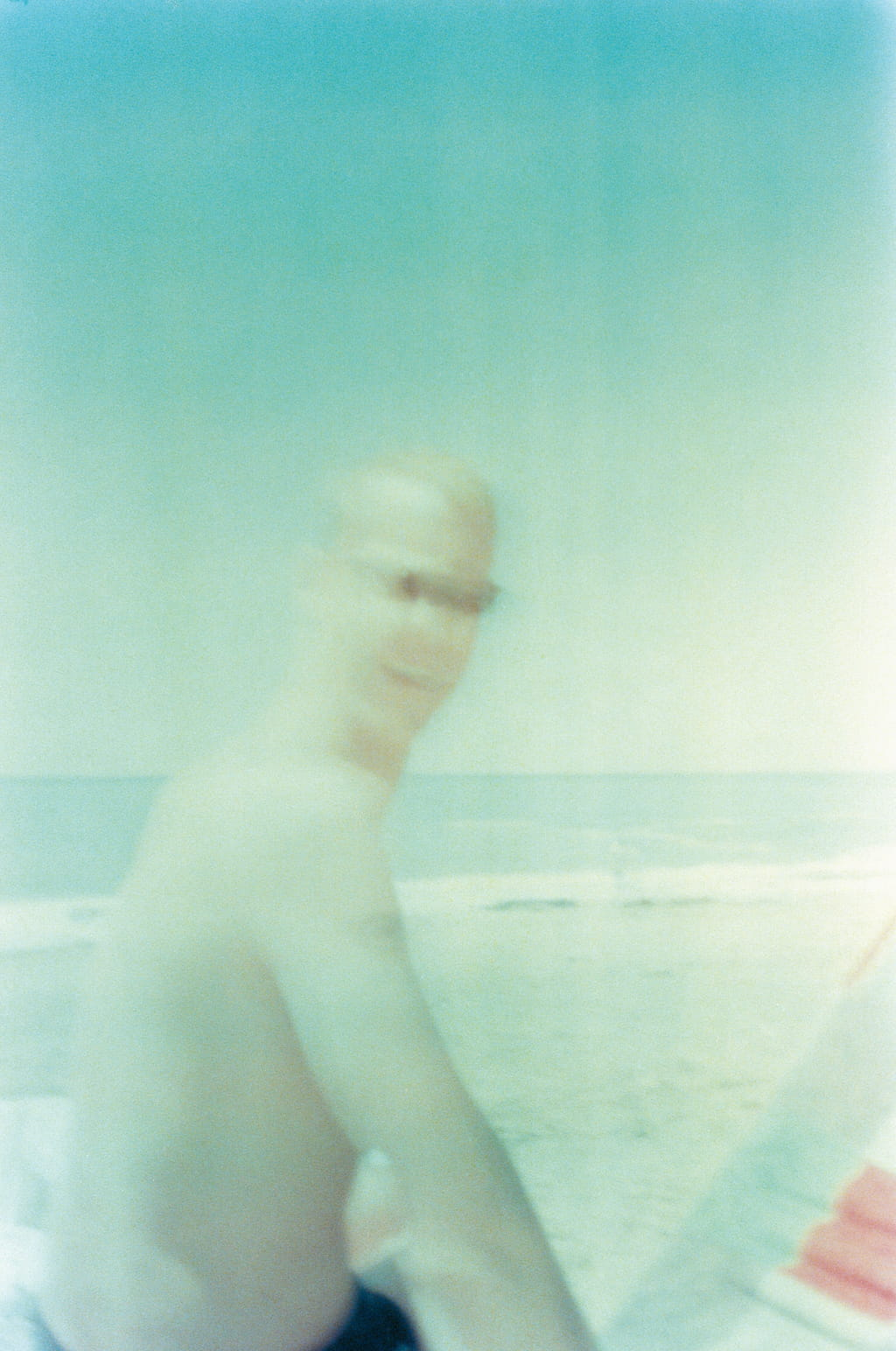 A photo of a man on the beach, he is moving and not in focus.