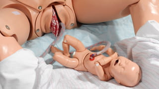Photo of two dolls, one of a woman giving birth, umbilical cord still attached to a baby doll.