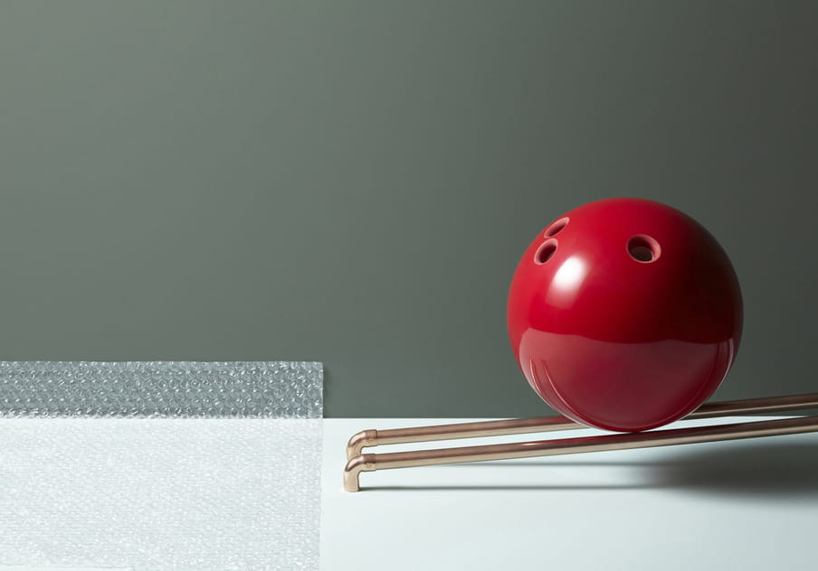 Colour photograph of a red bolling ball about to roll over a piece of bubble paper.