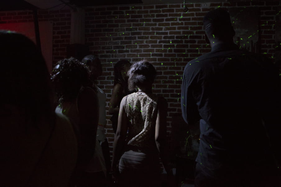 Photo taken in dark of some figures facing a brick wall with a little light on them, the wall covered in green dotted lights