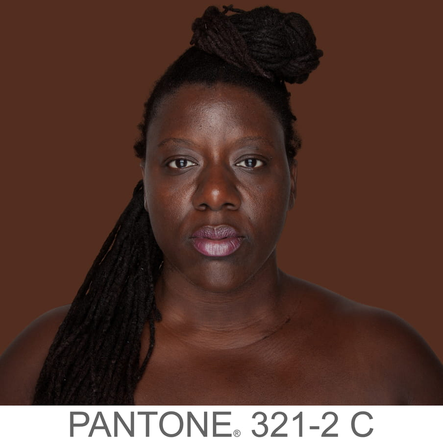 Photographic portrait of a woman with braids in a bun. The background is a sample of 11 x 11 pixels taken from the nose of the subject and matched with the industrial pallet Pantone®. The pantone color is written out as PANTONE 321-2C.