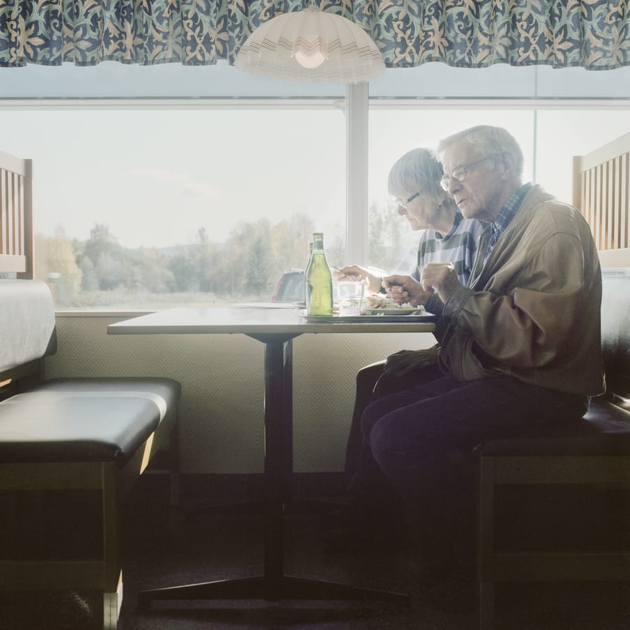 Elderly couple sits in a diner booth in front of a window that shows a green scenery. On the table there is a tray with food and drinks.