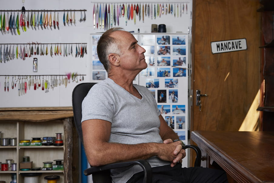 Photo of a man sitting in a room in a grey shirt - in the back fishing equipment and photos of him with fish