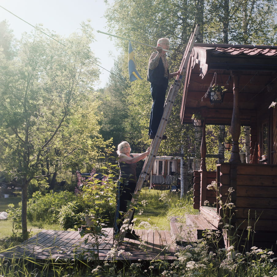 Photograph of an elderly couple on a ladder that stands against a wooden cabin. The man is holding a Swedish flag, that he want to attach to the cabin. The scene takes place in a green scenery with trees in the background and white flowers in the foreground.