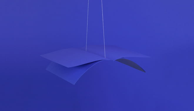 Photo of a few blue pages weaved together into a book, hanging from a string in the air - on a blue background