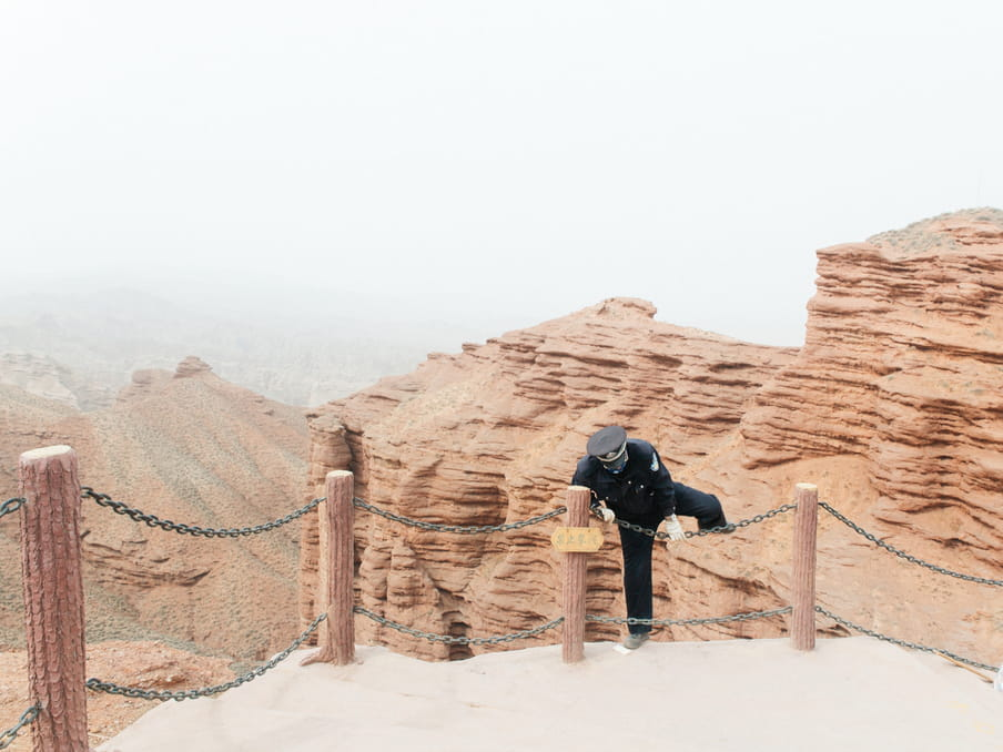 Photo of a man trespassing a limit in a rocky landscape