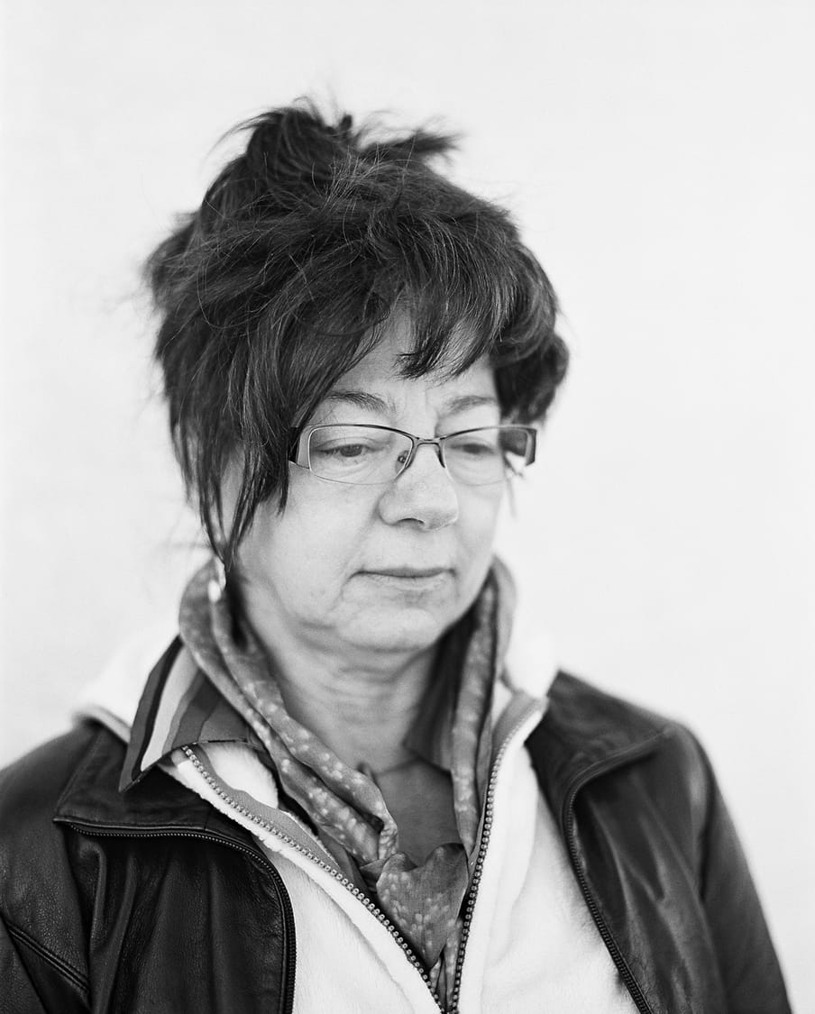 Black and white photo side profile of a person with short hair, falling around forehead and side of face as fringe, with glasses and a scarf collar, in a black leather jacket and zip up flece, eyes looking off to the right and down