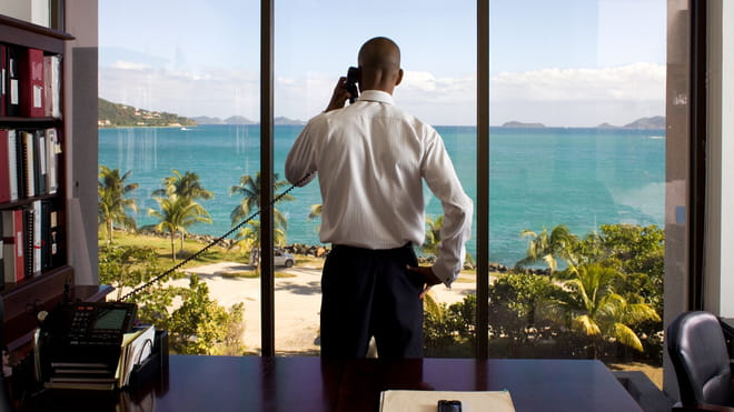 Photo of a man standing in an office in front of a window overlooking a bay with palm trees