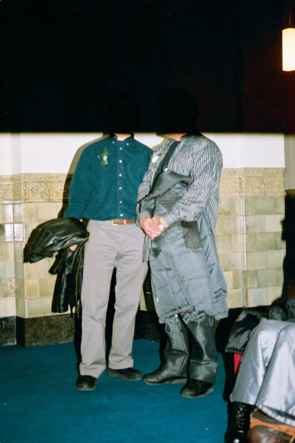 Two people posing for a photo in front of a brick wall. Due to the end of the film being reached the top of the photo is cut off and black.
