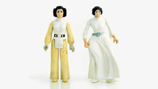 Two doll figures stand against a white background: on the left, a figure in a yellow outfit and white vest top and belt, with hair made up in buns around the ears, arms by the side. On the right, a similar looking figure, in a long-sleeved flowing white dress down to the ankles and green belt