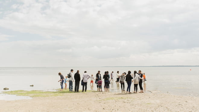 Photo of a group of people standing on a beach