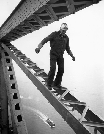 A construction worker balancing on a bridge girder high above San Francisco in California, c. 1955. Photo by Ernst Haas / Getty Images